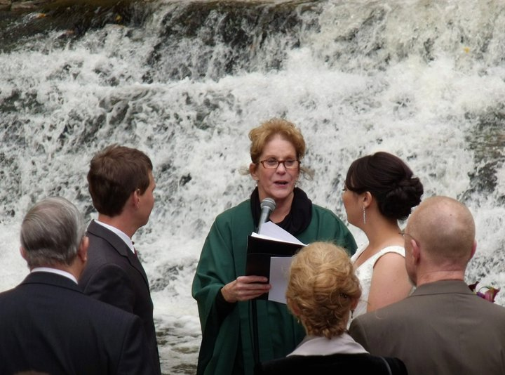 the minister giving the vows in front of the falls